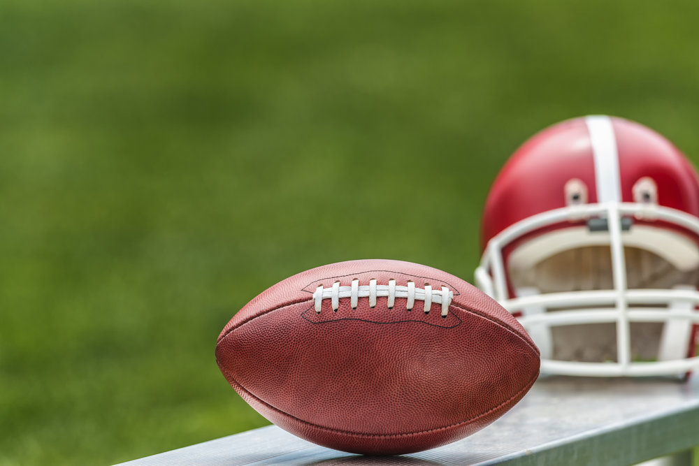 Selective focus of a Pro American leather football sitting on an aluminum bench along with a red football helmet and grass in the background.