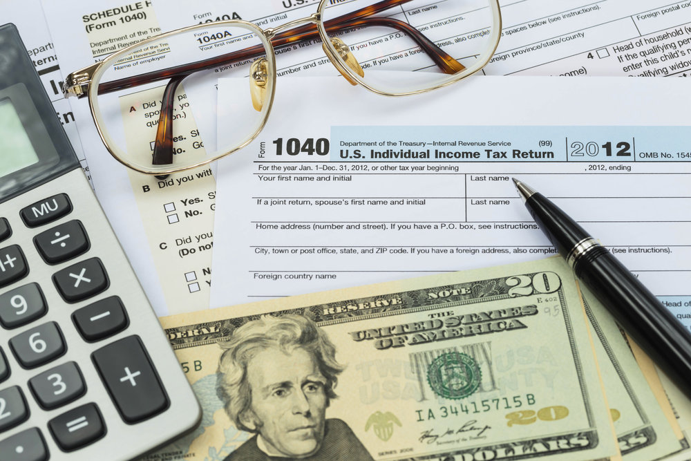 Tax form with pen, calculator, dollar banknote , and glasses taxation concept