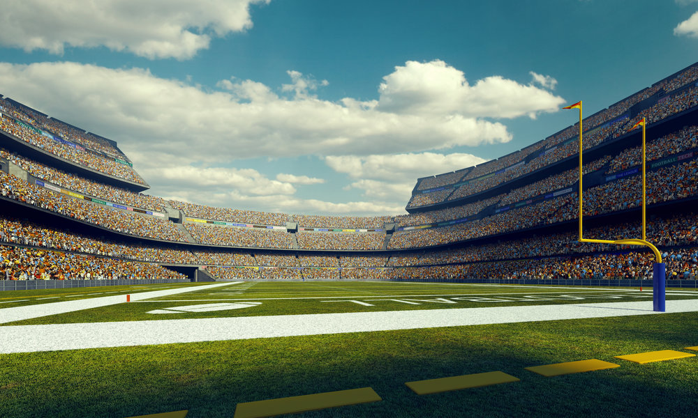 A wide angle panoramic image of a outdoor american football stadium full of spectators under blue sky. The image has depth of field with the focus on the foreground part of the pitch. The view from back line of the field.