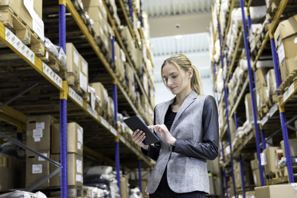 Portrait of a pensive young woman supervisor working on-line in warehouse. Young blond woman standing at distribution warehouse and wearing elegant suit. Industrial boss examining the stock. Large distribution storage in background with racks full of packages, boxes, pallets, crates ready to be delivered. Logistics, freight, shipping, receiving.
